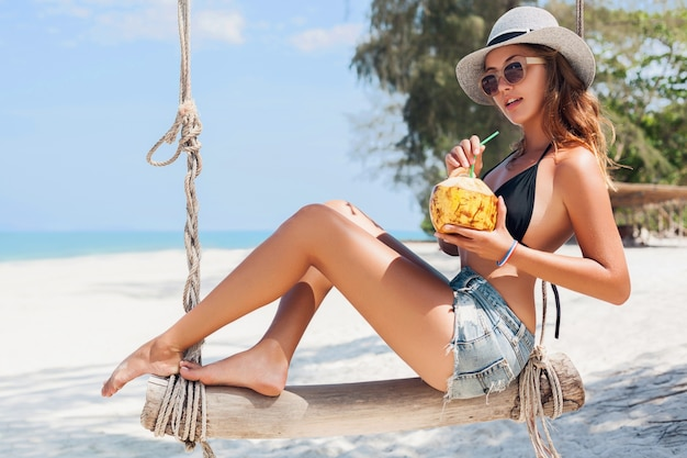 Jovem mulher sexy e atraente de férias sentada no balanço à beira-mar, praia tropical, bebendo coquetel no coco, pernas magras, viajando pela tailândia, sorrindo, feliz, emoção positiva, estilo verão