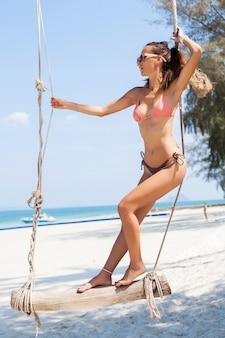 Jovem mulher sexy e atraente de férias sentada no balanço à beira-mar, praia tropical, pernas magras, viajando pela tailândia, sorrindo, feliz, emoção positiva, estilo verão