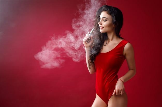 Jovem mulher sexy é vaping. uma nuvem de vapor. fotografia de estúdio.