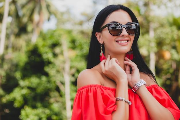 Jovem mulher sexy elegante com vestido vermelho de verão em pé no terraço de um hotel tropical, fundo de palmeiras, cabelo preto comprido, óculos de sol, brincos étnicos, óculos de sol, olhando para a frente, close-up