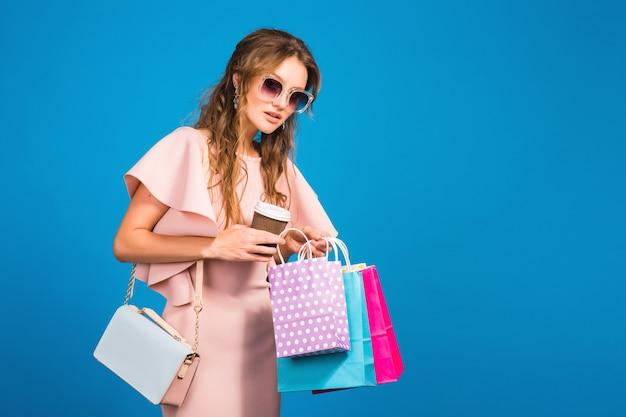 Jovem mulher sexy elegante em um vestido de luxo rosa, tendência da moda para o verão, estilo chique, óculos de sol, fundo azul studio, compras, segurando sacolas de papel, bebendo café, shopaholic