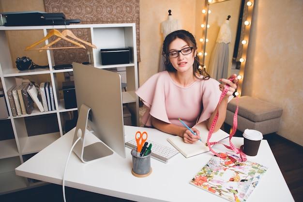 Jovem mulher sexy elegante em um vestido rosa de luxo, tendência de verão, estilo chique, estilista trabalhando no escritório no computador