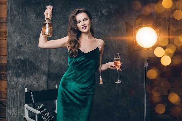 Jovem mulher sexy elegante nos bastidores do cinema, comemorando com uma taça de champanhe