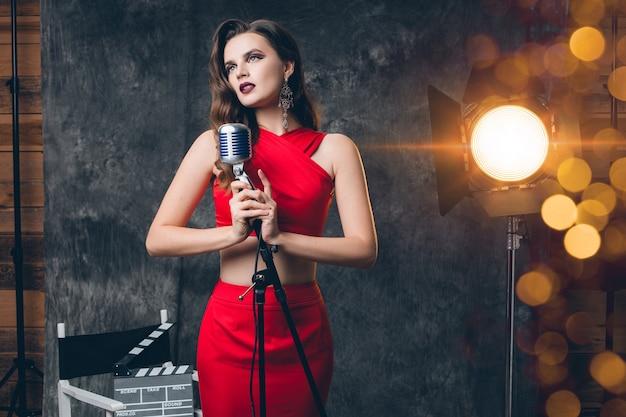 Jovem mulher sexy elegante nos bastidores do cinema, comemorando, vestido de noite de cetim vermelho