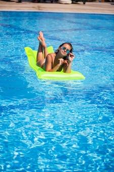 Jovem mulher sexy em um maiô nada na piscina em um colchão inflável. garota de óculos escuros em uma piscina azul de férias