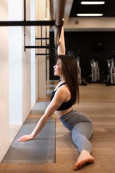 Jovem mulher sexy fazendo exercícios de alongamento no ginásio