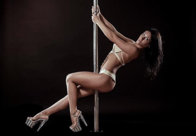 Jovem mulher sexy fazendo pole dance contra um fundo preto