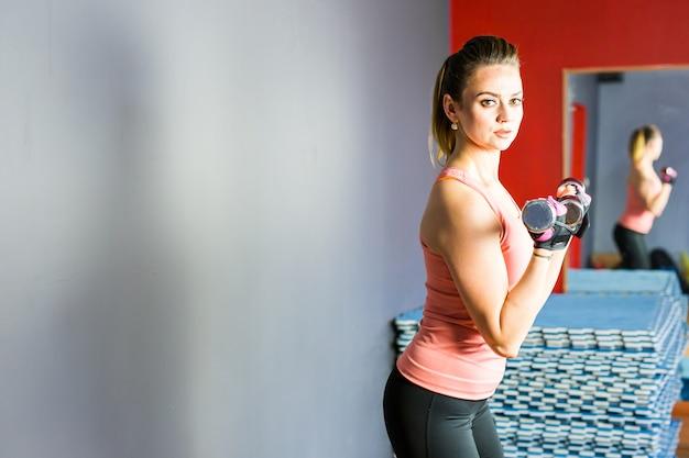 Jovem mulher sexy fitness fitness com halteres posando no fundo da parede.