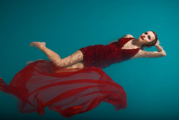 Jovem mulher sexy flutuando na piscina com vestido vermelho. tiro de beleza