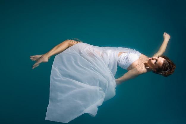 Jovem mulher sexy flutuando na piscina em um vestido branco. tiro de beleza