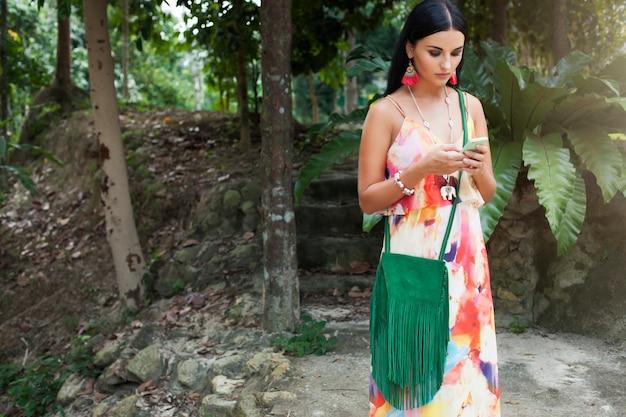 Jovem mulher sexy linda em um vestido colorido, estilo hippie de verão, férias tropicais, segurando um smartphone, mensagens de texto, brincos, mãos fecham