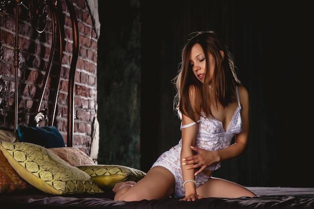 Jovem mulher sexy nua em cueca branca em uma cama vintage