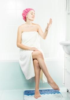 Jovem mulher sexy sentada no banheiro tomando banho