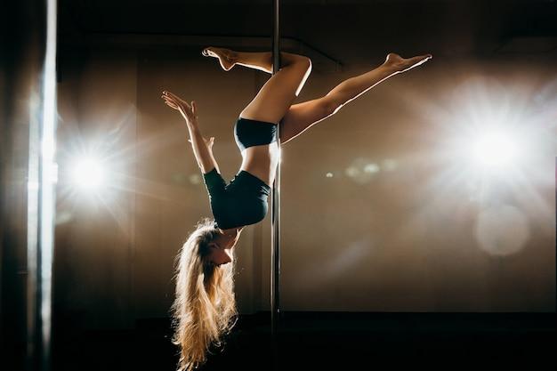 Jovem mulher sexy slim pole dançando no fundo escuro com luzes