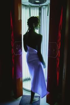Jovem mulher sexy tomando banho de sol no solário. morena atraente de biquíni está de pé no solário a trabalhar. cabine vertical para banhos de sol. linda mulher com pele bronzeada em salão de bronzeamento