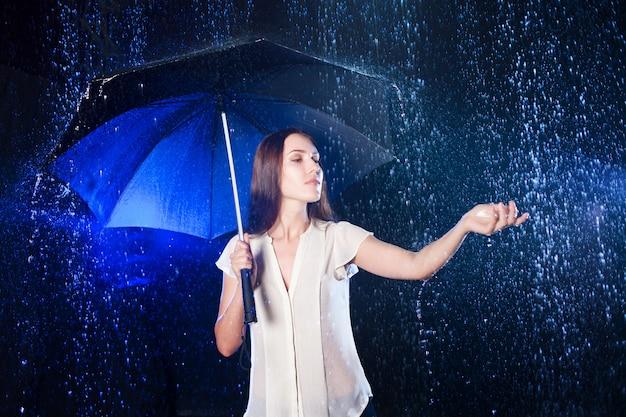 Jovem mulher sob o guarda-chuva. proteção contra chuva. toque a chuva
