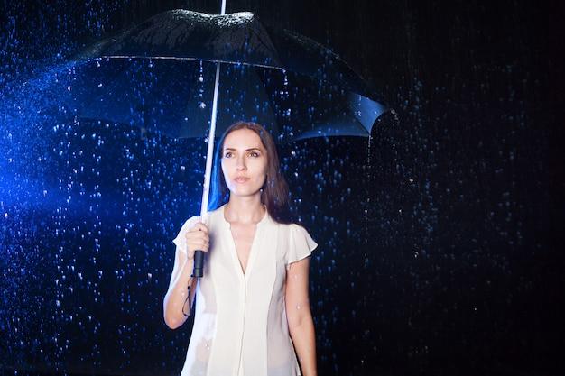 Jovem mulher sob o guarda-chuva. proteção contra chuva.