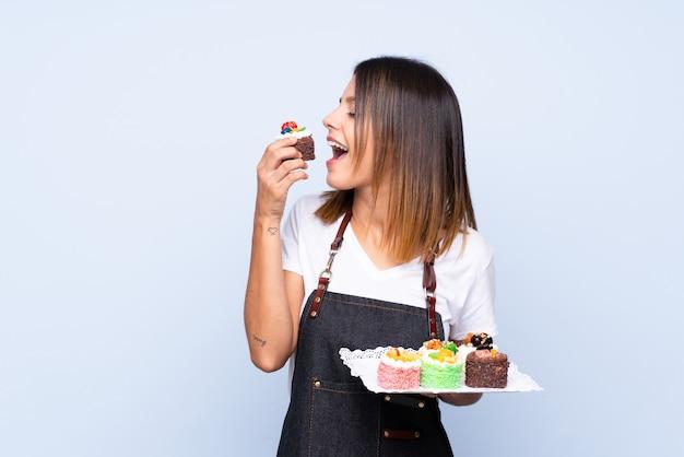 Jovem mulher sobre azul isolado segurando mini bolos e comê-lo