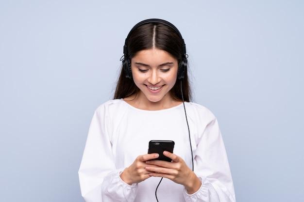 Jovem mulher sobre azul isolado usando o celular com fones de ouvido