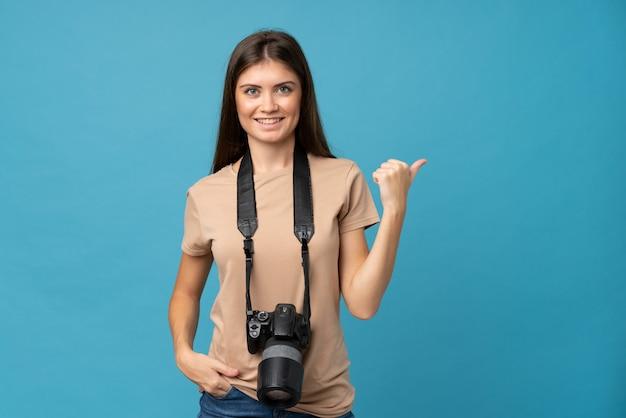 Jovem mulher sobre fundo azul isolado com uma câmera profissional e apontando para o lado