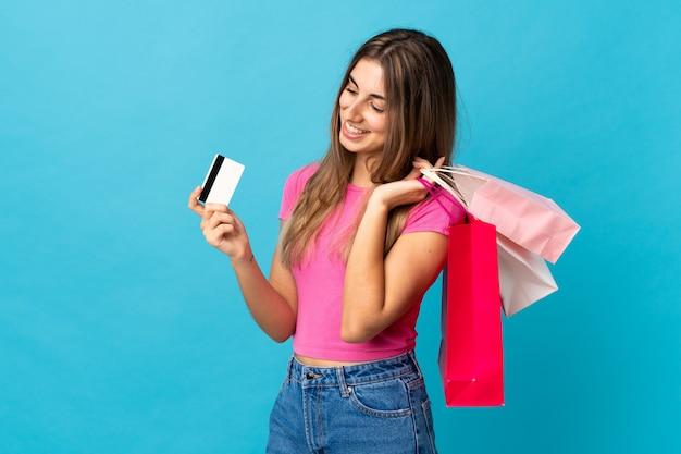 Jovem mulher sobre fundo azul isolado, segurando sacolas de compras e cartão de crédito