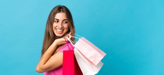 Jovem mulher sobre fundo azul isolado segurando sacolas de compras e olhando para trás
