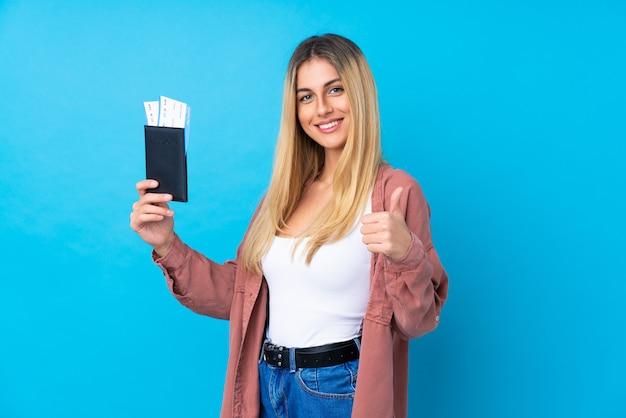 Jovem mulher sobre parede azul isolada em férias segurando um passaporte e avião com o polegar
