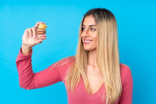 Jovem mulher sobre parede azul isolada segurando macarons franceses coloridos e com expressão feliz