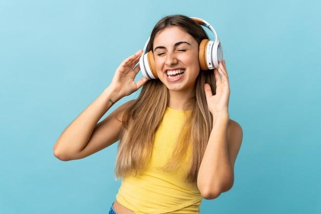 Jovem mulher sobre parede azul, ouvir música e cantar