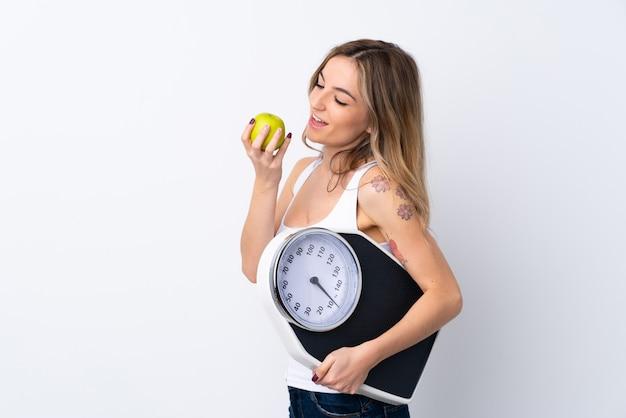 Jovem mulher sobre parede branca isolada com máquina de pesagem e com uma maçã