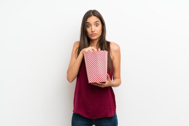 Jovem mulher sobre parede branca isolada, comendo pipocas