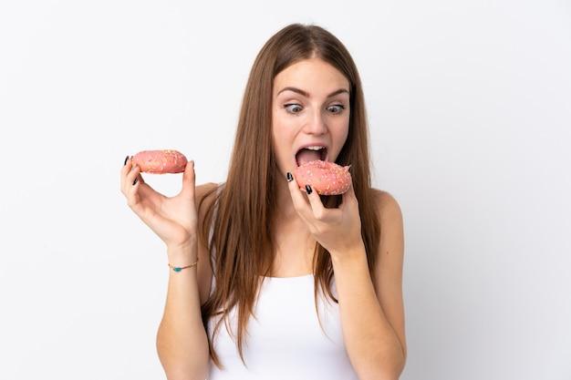 Jovem mulher sobre parede branca isolada, comendo um donut