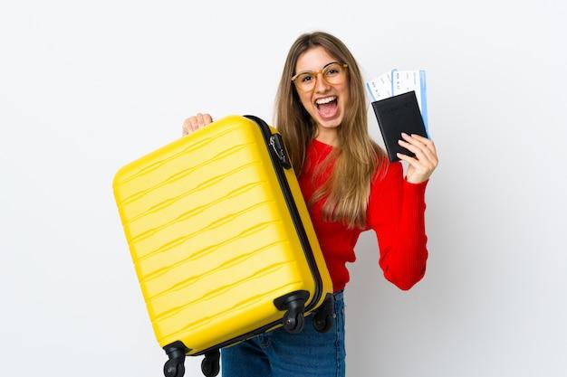 Jovem mulher sobre parede branca isolada em férias com mala e passaporte