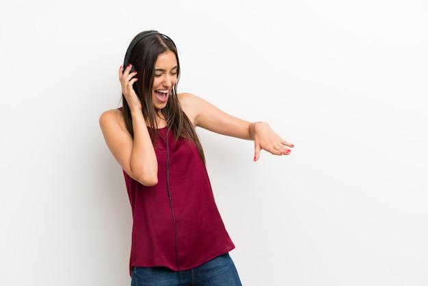 Jovem mulher sobre parede branca isolada, ouvindo música com fones de ouvido