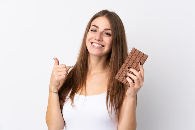 Jovem mulher sobre parede branca isolada, tomando um comprimido de chocolate e com o polegar