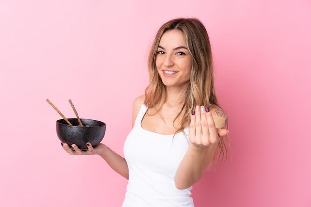 Jovem mulher sobre parede rosa isolada, convidando para vir com a mão. feliz que você veio segurando uma tigela de macarrão com pauzinhos