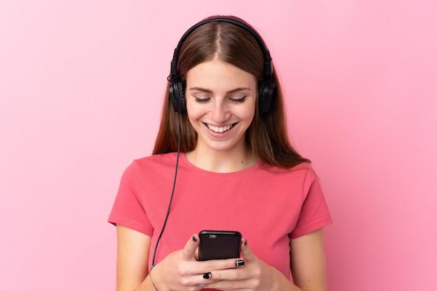 Jovem mulher sobre parede rosa isolada ouvindo música e olhando para o celular