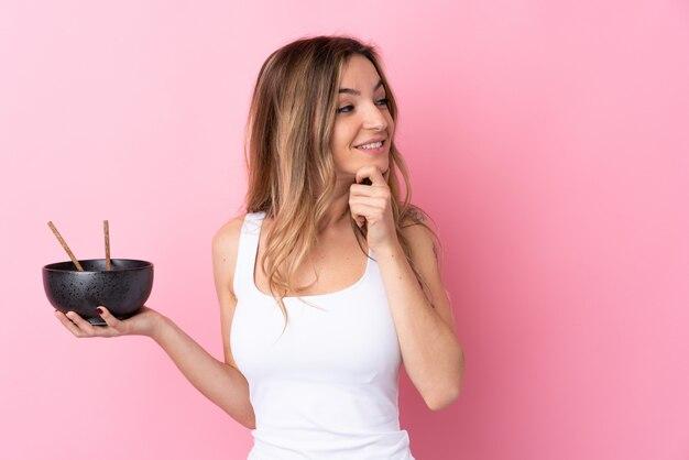 Jovem mulher sobre parede rosa isolada, pensando em uma idéia e olhando de lado enquanto segura uma tigela de macarrão com pauzinhos