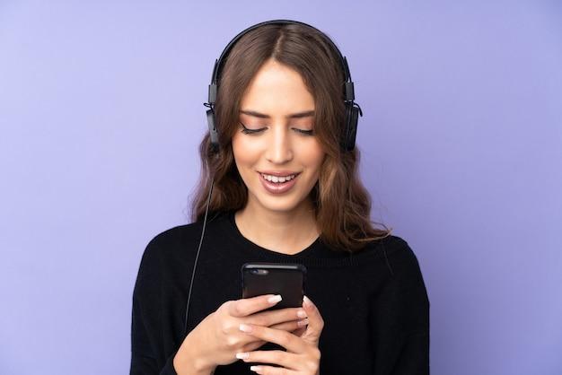 Jovem mulher sobre parede roxa, ouvindo música e olhando para o celular