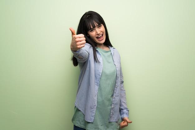 Jovem, mulher, sobre, parede verde, dar, um, polegares cima, gesto, porque, algo, bom, aconteceu