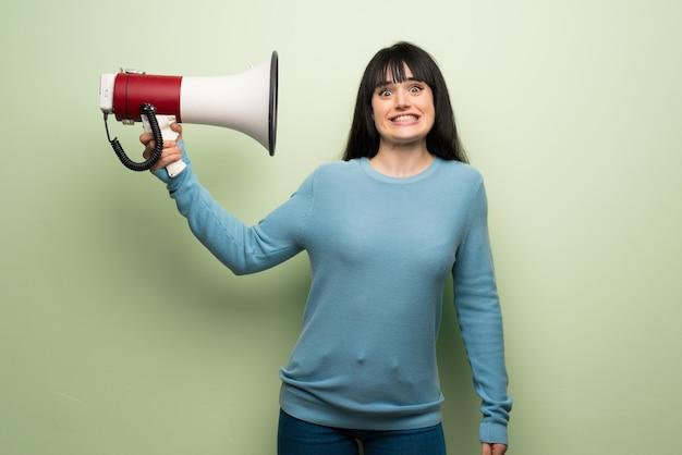 Jovem, mulher, sobre, parede verde, levando, um, megafone, que, faz, muito, barulho