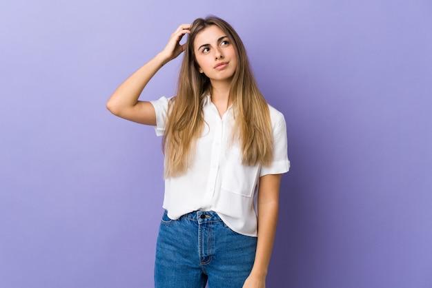 Jovem mulher sobre roxo isolado tendo dúvidas enquanto coçar a cabeça