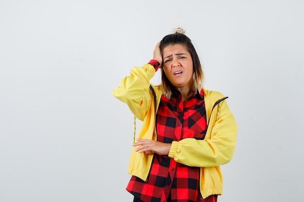 Jovem mulher sofrendo de dor de cabeça na camisa quadriculada, jaqueta e parecendo dolorida. vista frontal.