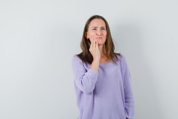 Jovem mulher sofrendo de dor de dente na blusa lilás e parecendo preocupada. vista frontal.