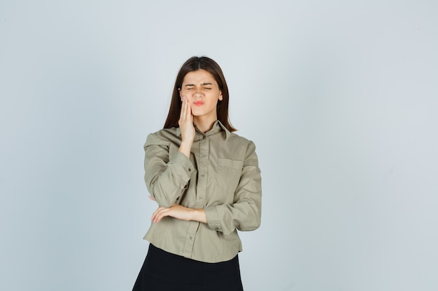 Jovem mulher sofrendo de dor de dente na camisa, saia e parecendo dolorida
