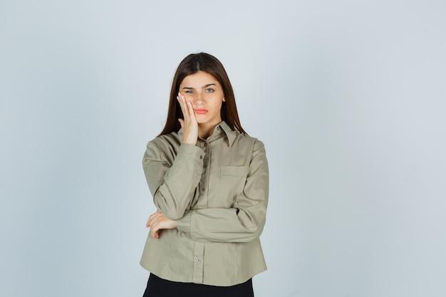 Jovem mulher sofrendo de dor de dente na camisa, saia e parecendo dolorosa, vista frontal.