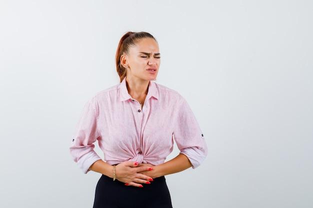 Jovem mulher sofrendo de dor de estômago em uma camisa casual, calças e parecendo doente. vista frontal.