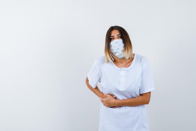 Jovem mulher sofrendo de dor de estômago na camiseta, máscara e aparentando indisposição. vista frontal.