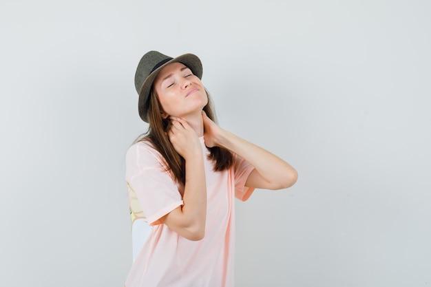 Jovem mulher sofrendo de dor no pescoço em t-shirt rosa, chapéu e parecendo desconfortável, vista frontal.