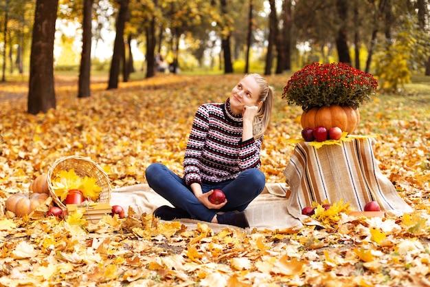 Jovem mulher sonha em um piquenique no parque com folhas de plátano